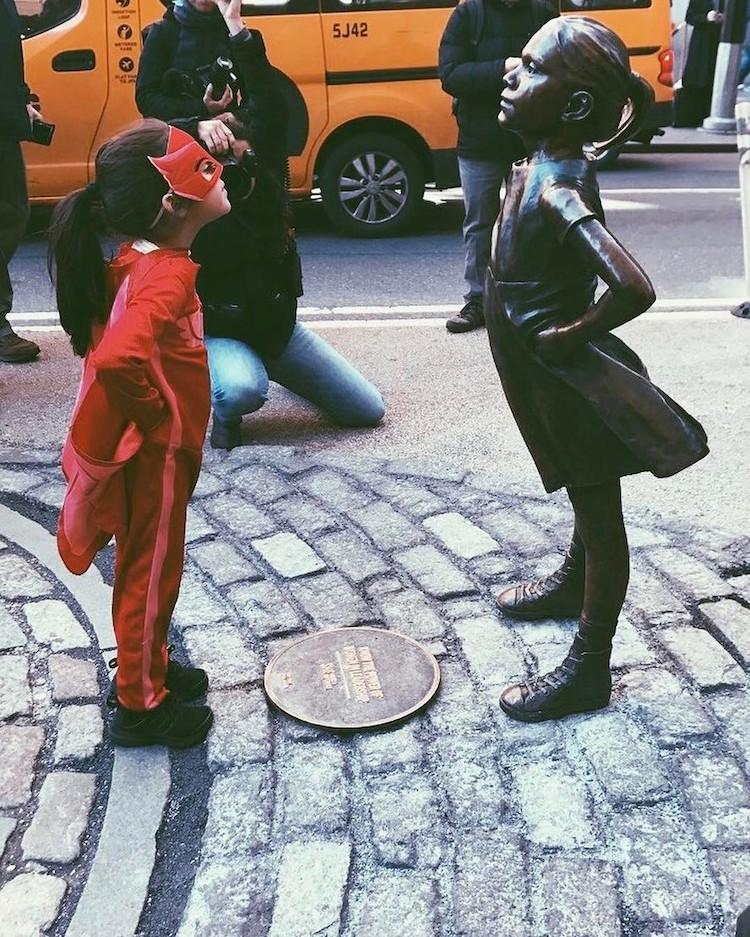 dziewczynka w stroju supermenki stoi na przeciw rzeźby fearless girl w nowym jorku